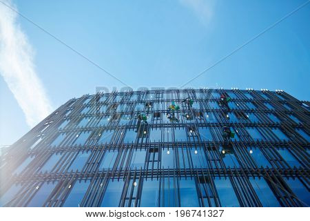 Upper part of modern office-building with maintenance service workers washing its windows
