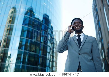 Happy specialist talking by mobile phone outdoors