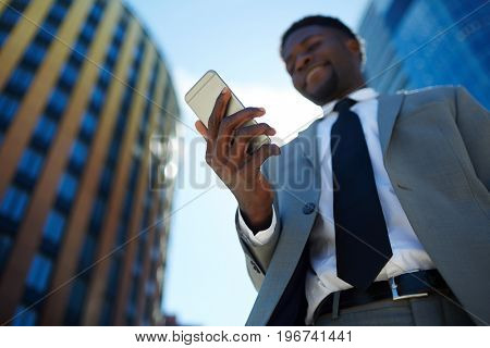 Smartphone in hand of African-american man in suit