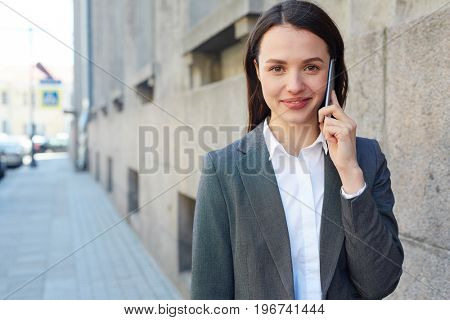 Pretty woman speaking on smartphone in the city