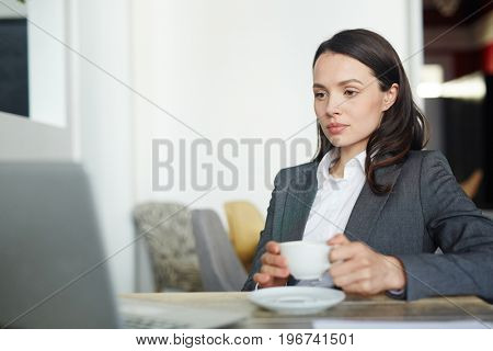 Serious woman with cup of tea reading online data