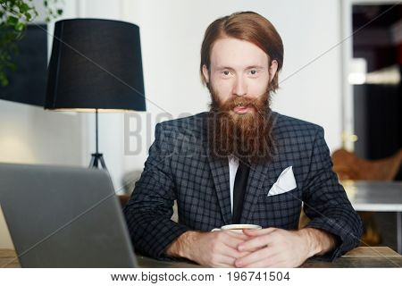 Bearded employer with cup of tea sitting in cafe