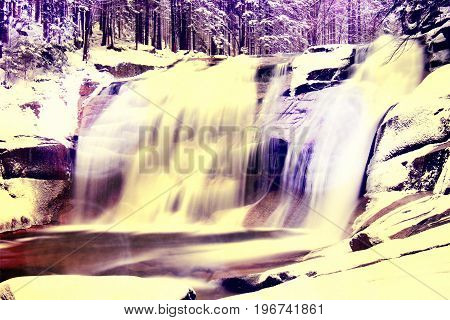 Film Effect. Winter View Over Snowy Boulders To Cascade Of Waterfall.. . Stream In Deep Freeze.
