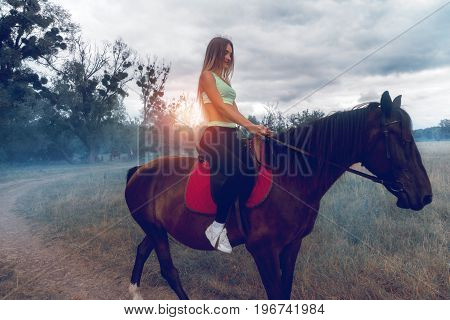 charming young lady very nice with massaging jets in sportswear on a horse