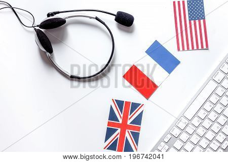 Learning languages online. Headphones and keyboard on white table background top view.