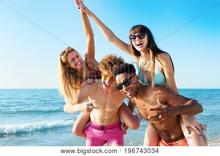 Cheerful young friends giving piggyback rides to girlfriends and enjoying summertime on the beach