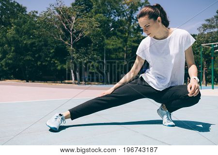 Young athletic girl doing stretching legs at the playground in summer