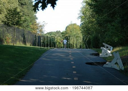 Albion Rhode Island USA - September 10 2006: Runner tops short hill on Blackstone River Bikeway