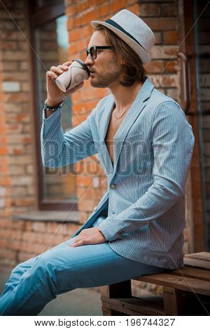 Young man in modern clothes is sitting on the street and drinking coffee. Outdoor fashion.