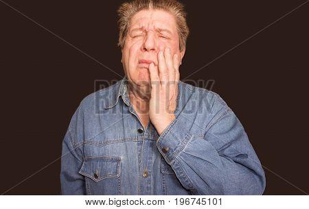 The caucasian senior man with teeth pain at studio on black background