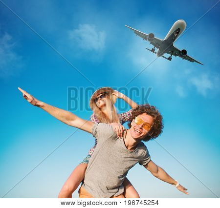 Happy smiling couples playing at the sunny beach with aircraft in the sky