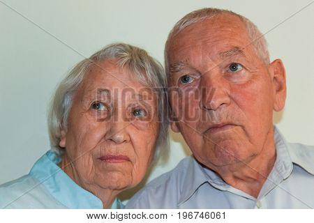 The happy elderly couple on the studio background looking away. The concept of fear