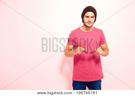 Stylish guy with stubble wearing brown hat, pink t-shirt and jeans holding sunglasses and looking away.