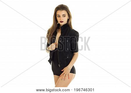 slender young lady in black body stands in the Studio in front of a camera isolated on white background