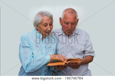 The happy elderly couple on the studio background reading book