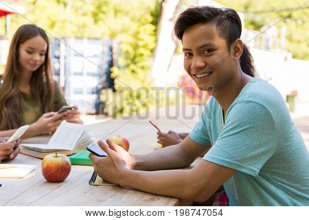 Photo of smiling young multiethnic friends students outdoors using mobile phones. Asian man looking camera.