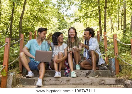 Picture of young multiethnic friends students outdoors using mobile phone and laptop computer and talking with each other. Looking aside.