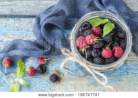 Fresh berries of raspberries and blackberries in a glass jar on a wooden table, top view