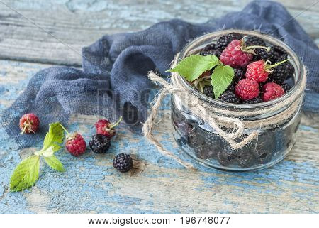 Fresh berries of raspberries and blackberries in a glass jar on a wooden table