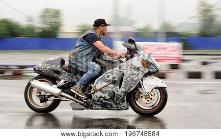 Orel Russia July 22 2017: Dynamica car festival. Man riding motorcycle in rain motion blur