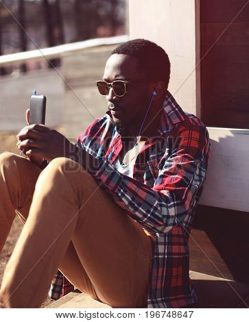 Fashion Portrait Young African Man Listens To Music Using Smartphone, Wearing A Hipster Plaid Red Sh
