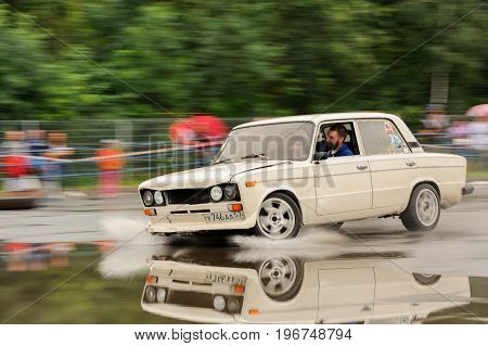 Orel Russia July 22 2017: Dynamica car festival. White tuned Russian car VAZ Lada rides on puddles and reflects in wet asphalt motion blur