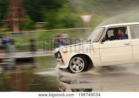 Orel Russia July 22 2017: Dynamica car festival. White tuned Russian car VAZ Lada rides at full speed on puddles and splashes water with reflections and motion blur