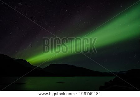 Northern lights at night over a lake in Igaliko Greenland
