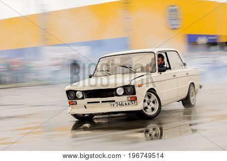 Orel Russia July 22 2017: Dynamica car festival. White tuned Russian car VAZ Lada swiftly drift rides on wet asphalt with industrial background motion brur