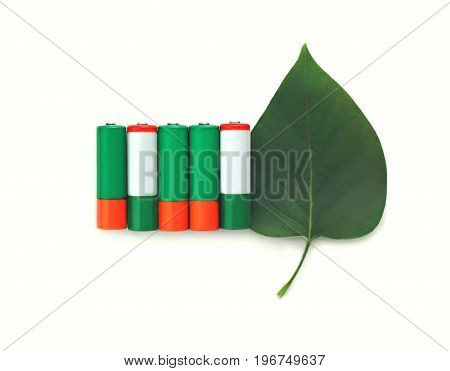 Recycling, Energy, Environment And Ecology Concept - Close Up Of Green Alkaline Batteries With Leaf