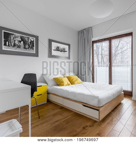 White multifunctional bedroom with desk double bed and big balcony door