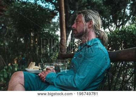 Profile View Of Casual Man With Long Blond Hair Sitting Outdoor During Summer Vacation.