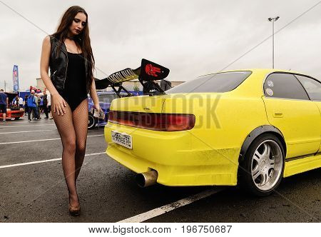 Orel Russia July 22 2017: Dynamica car festival. Long haired girl in black bikini wolking near new yellow car