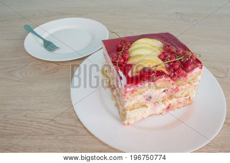 Sliced tasty cake on wooden table background. Piece cake on white plate with fork