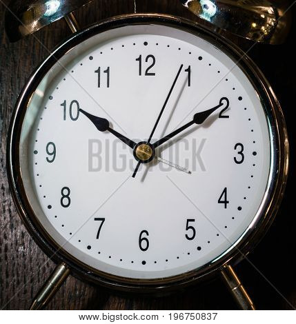 Classical alarm clock ringing on wooden background.