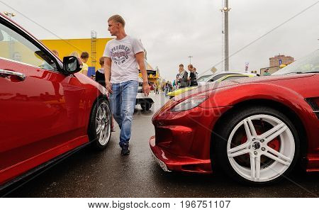 Orel Russia July 22 2017: Dynamica car festival. Tuned new red cars and wolking man