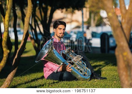 Musician with the tuba sitting on the grass in the Park.