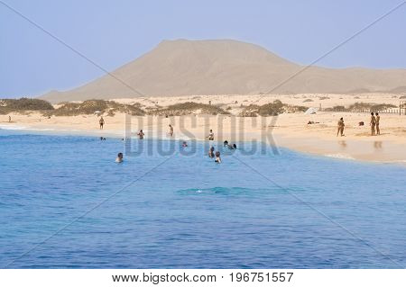 Badende Touristen im Meer vor der Küste von Fuerteventura in Spanien