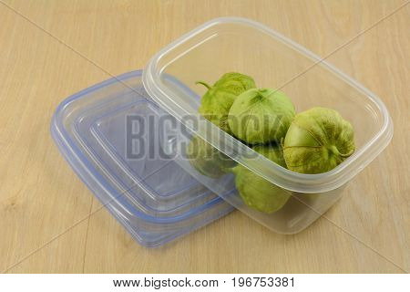 Green tomatillos in husks in plastic refrigerator storage container on wooden table