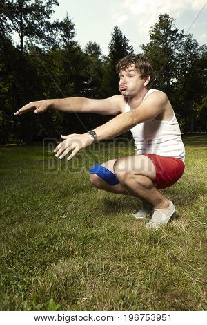 Funny weak man in retro style exercising in summer park
