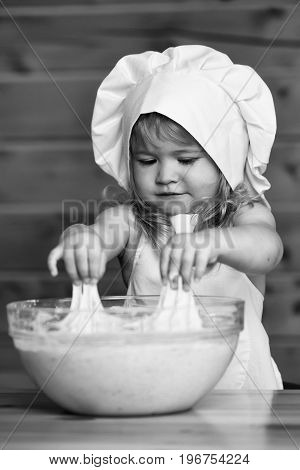 small child with happy face in cook uniform with chef hat and apron kneading dough with flour in glass bowl in kitchen on wooden or wood background black and white