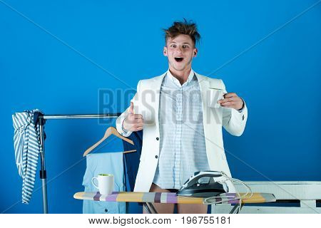 Man with happy face and messy hair showing thumbs up hand gesture. Macho in shirt jacket and underpants with cup. Ironing board with iron and clothes rack on blue background. Fashion concept