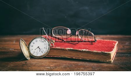 Vintage Book And Pocket Watch On Dark Background