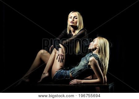 Twins on black background. Women with blonde hair. Girls with pretty face. Freedom and lgbt. Beauty and fashion.