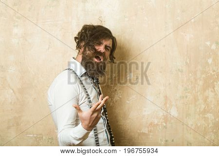 Business fashion and beauty. Fashion model with stylish hair. Guy or businessman at textured wall. Man with long beard and mustache on shouting face. Hipster in shirt and suspenders with musical tie.