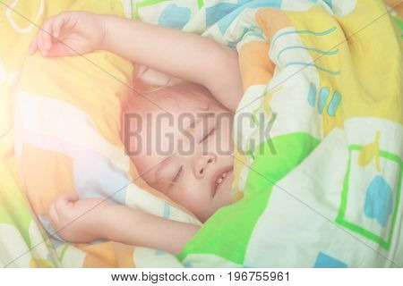 Child sleep in bed. Sleepy baby in colorful blanket. Childhood and happiness. Trust and tenderness. Small baby dreaming.