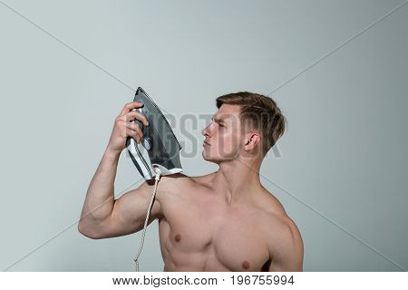 Man with muscular body hold iron. Guy in wardrobe. Everyday life and housework. Housekeeping and household. Macho ironing clothes.