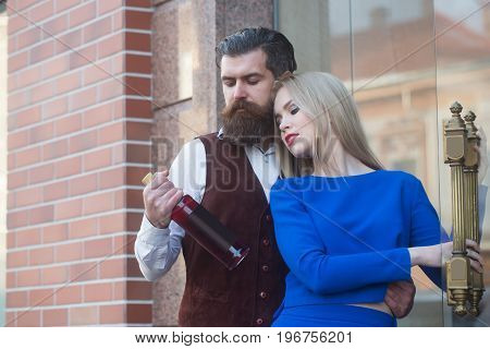 Couple in love looking at bottle of wine. Man or hipster hugging sexy woman or girl in blue dress outdoors on brick wall. Alcohol and convive. Unhealthy lifestyle. Bad habits