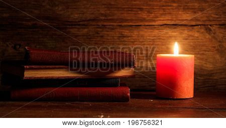 Vintage Books And A Candle On Wooden Background