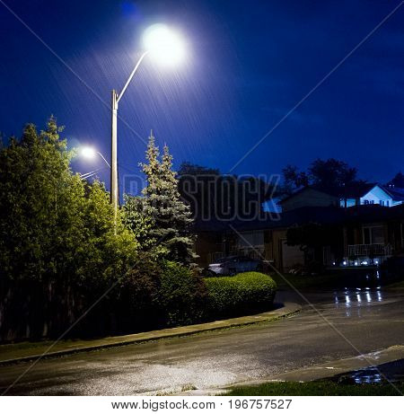 Rain Pouring Down On Stormy Night, Residential Street With Water Lit By Lamp Post